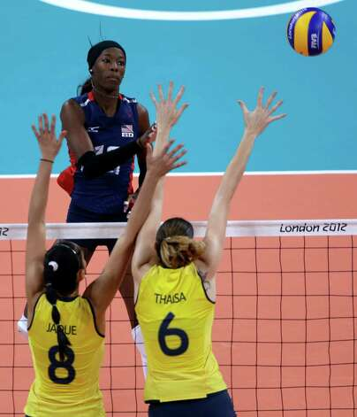 United States' Destinee Hooker, top, spikes the ball over Brazil's Jaqueline Carvalho (8) and Thaisa Menezes (6) during a women's gold medal volleyball match at the 2012 Summer Olympics, Saturday, Aug. 11, 2012, in London. (AP Photo/Jeff Roberson) Photo: Jeff Roberson, Associated Press / AP