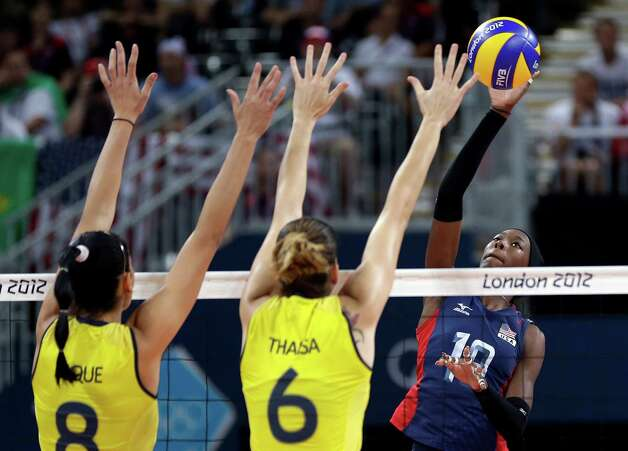 USA's Destinee Hooker (19, right) prepares to smash the ball past Brazil's Jaqueline Carvalho (8) and Thaisa Menezes (6) during a women's volleyball gold medal match at the 2012 Summer Olympics Saturday, Aug. 11, 2012, in London. (AP Photo/Chris O'Meara) Photo: Chris O'Meara, Associated Press / AP