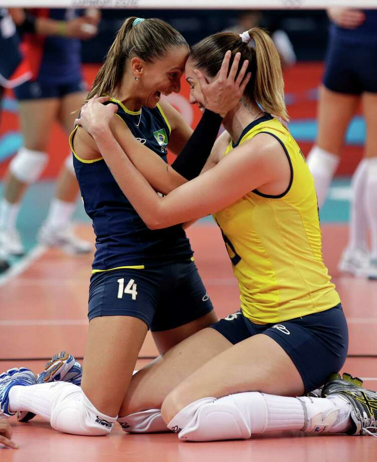 Brazil's Fabiana Oliveira celebrates with Thaisa Menezes after defeating the United States 3 sets to 1 during the women's gold-medal volleyball match Saturday. (AP Photo/Dave Martin) Photo: Ap/getty