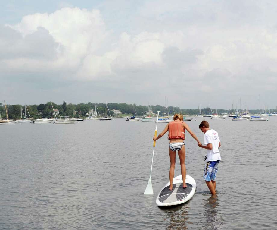 At left, Kim Heaney of Michigan, gets a paddleboard lesson from Greenwich Community Sailing instructor Billy Ridenour in Greenwich Cove, Saturday, Aug. 11, 2012. Photo: Bob Luckey / Greenwich Time