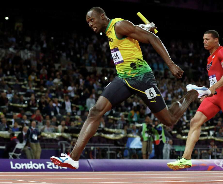 Jamaica's Usain Bolt, left, crosses the finish line ahead of Ryan Bailey of the United States in the men's 4x100-meter relay final during the athletics in the Olympic Stadium at the 2012 Summer Olympics, London, Saturday, Aug. 11, 2012. Jamaica set a new world record with a time of 36.84 seconds. (AP Photo/David J. Phillip) Photo: David J. Phillip / AP