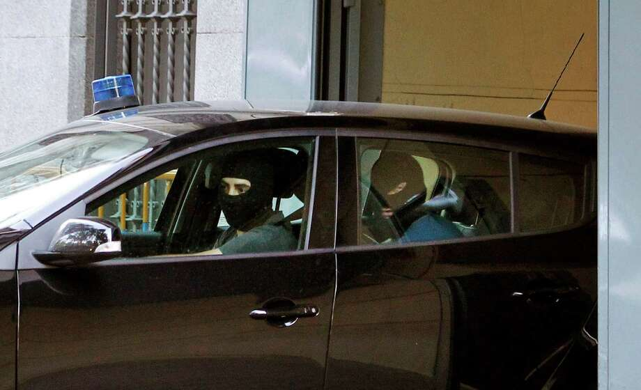 Police reverse the car carrying one of the two Russian Islamist terror suspects (out of view) to the National Court, as confirmed by court officials in Madrid, Spain, Sunday, Aug. 5, 2012. Spanish police arrested three suspected members of al-Qaida who they believe were planning to carry out attacks in Spain and possibly other European countries, Interior Minister Jorge Fernandez Diaz said Thursday. He said the three men were detained Wednesday. Two of the detainees were from countries of the former Soviet Union and were arrested in the central town of Ciudad Real. The third, a Turk, was detained in the southern town of La Linea. (AP Photo/Andres Kudacki) Photo: Andres Kudacki