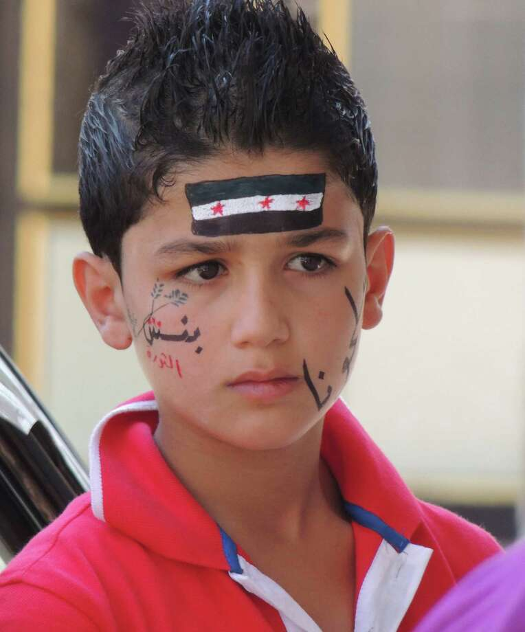 """This citizen journalism image released by the Shaam News Network and accessed Saturday, Aug. 11, 2012 purports to show a young protester in the village of Binnish in Idlib province, Syria, Friday, Aug. 10, 2012. Arabic on boy's face reads """"Binnish--the revolution.""""  (AP Photo/Shaam News Network) THE ASSOCIATED PRESS IS UNABLE TO INDEPENDENTLY VERIFY THE AUTHENTICITY, CONTENT, LOCATION OR DATE OF THIS HANDOUT PHOTO Photo: Anonymous"""