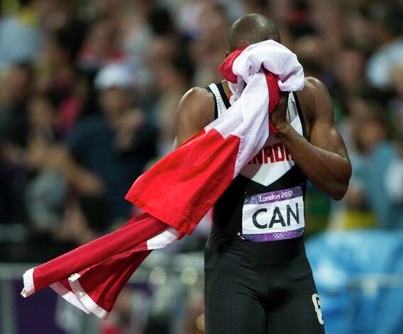 Canada's Oluseyi Smith cries into a flag after the team was disqualified from a third-place finish in the men's 4x100-meter relay on Saturday.. (AP Photo/The Canadian Press, Ryan Remiorz) Photo: Ap/getty