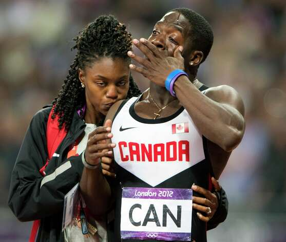 Canada's Justyn Warner is comforted after the team was disqualified from third place in the men's 4x100-meter relay, for running outside its lane. (AP Photo/The Canadian Press, Ryan Remiorz) Photo: Ap/getty