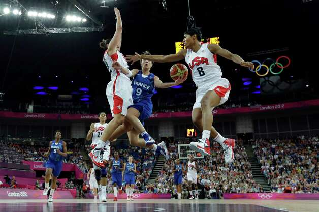 France's Celine Dumerc  drives to the basket as United States' Diana Taurasi, left, and Angel McCoughtry (8) during the gold-medal game Saturday. The U.S. won 86-50. (AP Photo/Eric Gay) Photo: Ap/getty