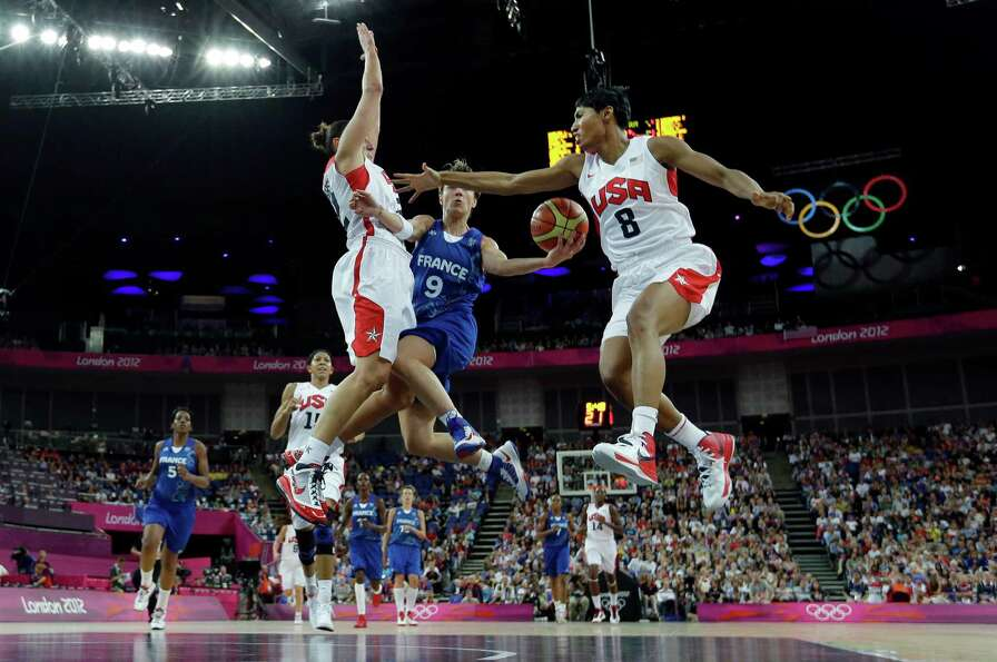 France's Celine Dumerc  drives to the basket as United States' Diana Taurasi, left, and Angel McCou