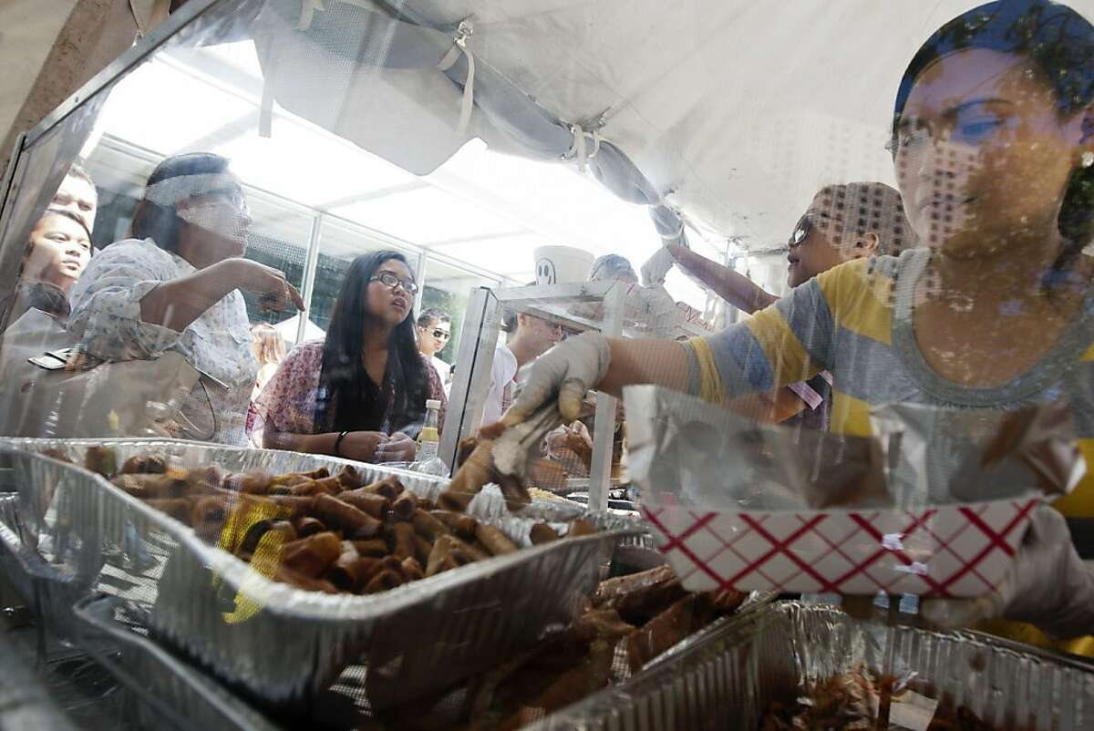 Annette Guevarra, with Pampanga's Cuisine, serves up lumpia to guests at the Pistahan Festival, a celebration of Filipino culture, art, dance, music, and food, at Yerba Buena Gardens in San Francisco, Saturday, August 11, 2012.