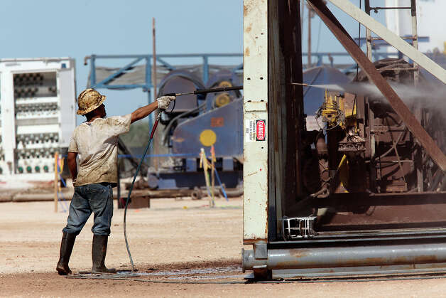 A roustabout worker washes a drilling rig at a lease off Loving County Road 408 near Mentone, Texas, Wednesday, July 25, 2012. Located 130 miles west of Midland, Texas, the county has a permanent population of about 85. Around 1,000 to 1,500 people work the oil fields in the county during working hours. The county has no paved county roads according to County Judge Skeet Jones. In the last four years, the county has spent $350,000 a year maintaining them. Photo: Jerry Lara, San Antonio Express-News / © 2012 San Antonio Express-News