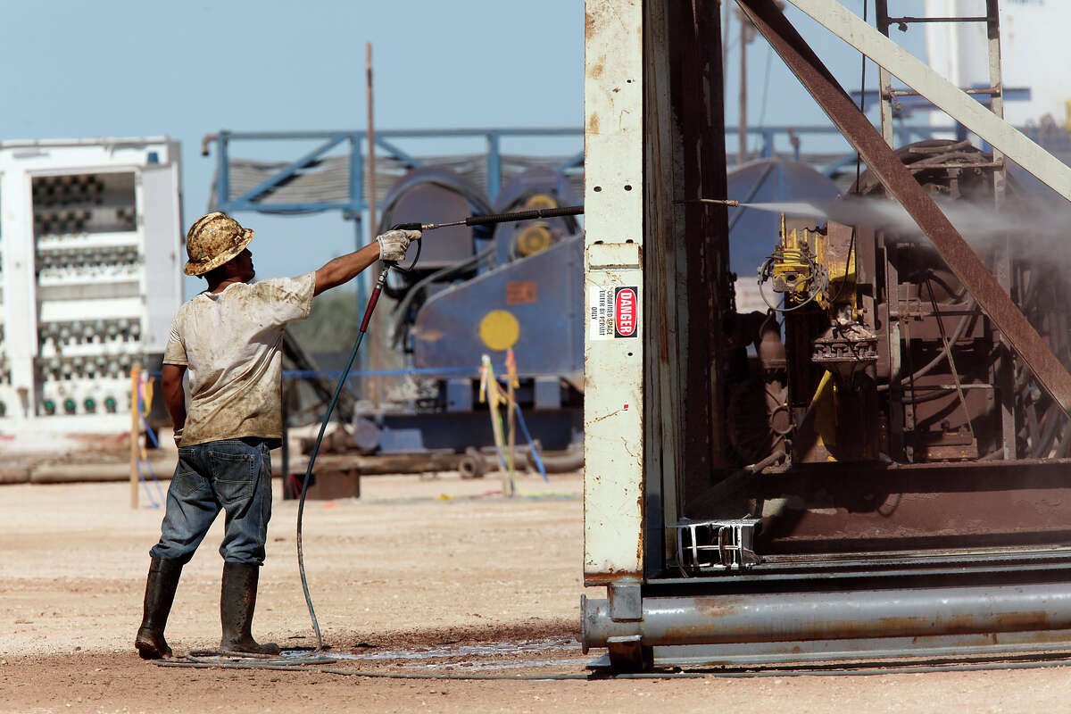 A roustabout worker washes a drilling rig at a lease off Loving County Road 408 near Mentone, Texas, Wednesday, July 25, 2012. Located 130 miles west of Midland, Texas, the county has a permanent population of about 85. Around 1,000 to 1,500 people work the oil fields in the county during working hours. The county has no paved county roads according to County Judge Skeet Jones. In the last four years, the county has spent $350,000 a year maintaining them.