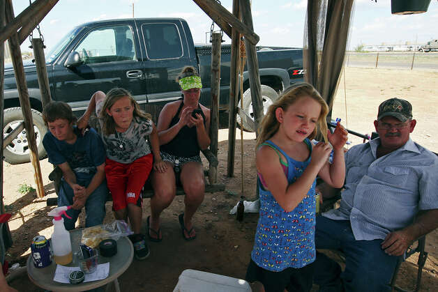 "Visiting her grandparents for part of the summer, Darbi Doan, 8, second from left, hangs out with neighbors under a canopy at the E&D RV Park near Stanton, Texas, Wednesday, July 25, 2012. Doan's grandparents pay $400 a month for a slot at the park. ""We've been living here six months. This is our living room,"" said Doan's grandmother, Toni Robertson. With Doan are from left, Braxton Vick, 17, Jordan Vick, 14, Dene Vick, 36, and Connor Howell, 45. Photo: Jerry Lara, San Antonio Express-News / © 2012 San Antonio Express-News"