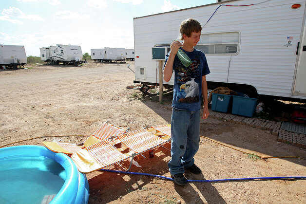 Braxton Vick, 17, cools off with a mister at the E&D RV Park near Stanton, Texas, Wednesday, July 25, 2012. With the oil and gas boom around the Permian Basin, housing is scares and expensive. Slots at the park go for $400 a month. Photo: Jerry Lara, San Antonio Express-News / © 2012 San Antonio Express-News