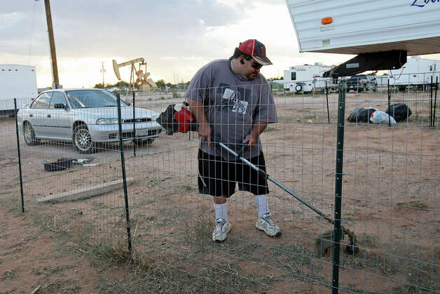 Jay Saravo cleans up his lot at a RV park in Midland, Texas, Wednesday, July 25, 2012. In back is a pump jack, a familiar sight in the Permian Basin. Photo: Jerry Lara, San Antonio Express-News / © 2012 San Antonio Express-News