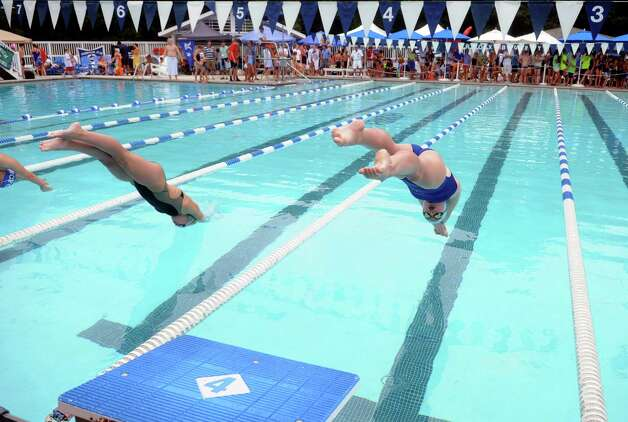 Quinn Scanlan, right, of the Stamford Yacht Club, dives off the block to compete in the girls 14 and under 100 SC meter individual medley during the Fairfield County Swim League Championshps at Roxbury Swim and Tennis Club in Stamford on Saturday, August 11, 2012. Photo: Lindsay Niegelberg / Stamford Advocate