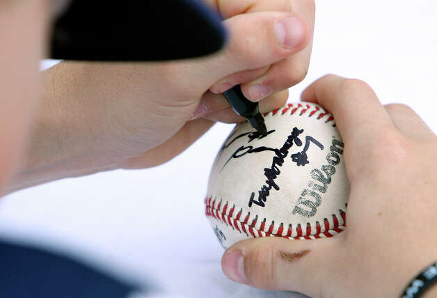 McAllister Park Little League All-Stars' Kyle Pollard autographs a ball after the river parade celebration Sunday, Sept. 6, 2009. Photo: Edward A. Ornelas, San Antonio Express-News / eaornelas@express-news.net