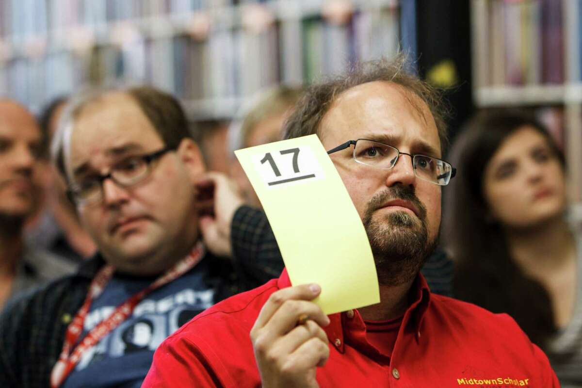 """Eric Papenfuse places a bid during Larry McMurtry's 300,000 book auction """"The Last Book Sale"""" at Booked Up No. 4, Friday, Aug. 10, 2012, in Archer City."""