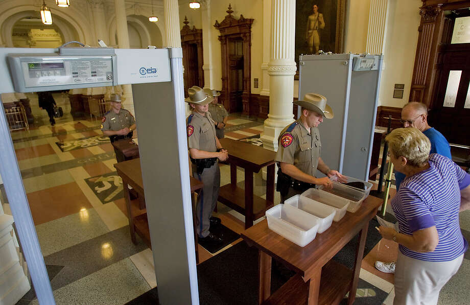 5/21/10 Ralph Barrera/AMERICAN-STATESMAN; Without fanfare, the first step to airport-style security checkpoints were opened at the four entrances to the Texas Capitol Friday morning. The public, visitors and lobbyists must walk through metal detectors and have their purses and briefcases searched. In coming weeks, their belongs will have to go through X-ray machines yet to be installed. State employees can walk around the checkpoint if they show a valid state ID, as can Texans who carry a concealed pistol with a permit. (Ward story) Photo: Ralph Barrera, Austin American-Statesman / Austin American-Statesman