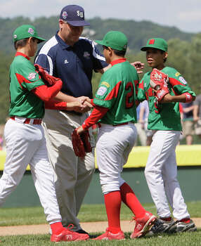 McAllister Park Little League Mananger Mike Shull congratulates Reynosa, Mexico, players Marcelo Martinez (from left), Jorge Maldonado and Oscar Noguera after Mexico won 5-4 in the Consolation Game of the 2009 Little League World Series on Sunday, Aug. 30, 2009 in South Williamsport, Pa. Photo: Jerry Lara, San Antonio Express-News / glara@express-news.net