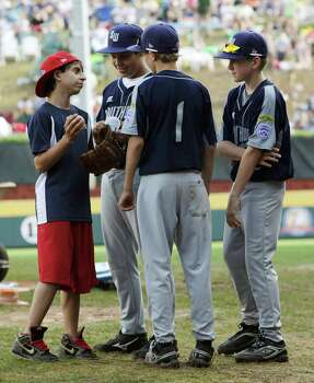 "Moises Arias, aka Rico Suave from ""Hannah Montana,"" talks with McAllister Park Little League players Travis Daves (from left), Wyatt Willis and Kyle Pollard during a game delay of their game against Chula Vista, Calif. in the U.S. Championship game of the 2009 Little League World Series on Saturday, Aug. 29, 2009 in South Williamsport, Pa. Photo: Jerry Lara, San Antonio Express-News / glara@express-news.net"