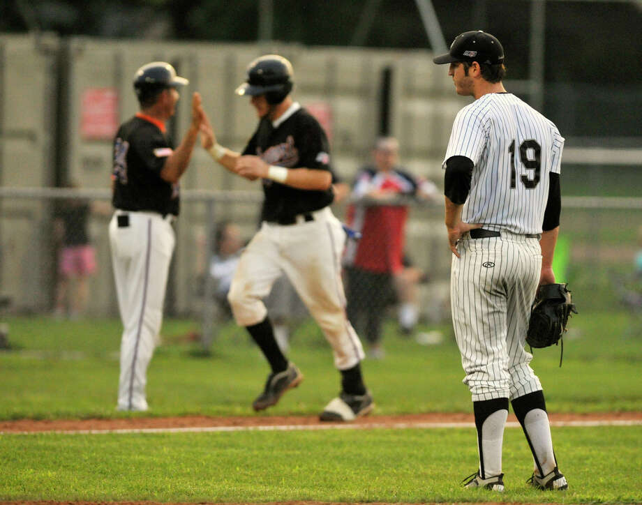 Newport's Kasey Coffman, center, rounds the bases as Danbury starting pitcher Stephen Catalina, right, looks on after Coffman hit a three-run home run in the fifth inning of game two of their NECBL championship game at Rogers Park in Danbury on Saturday, Aug. 11, 2012. Photo: Jason Rearick / The News-Times