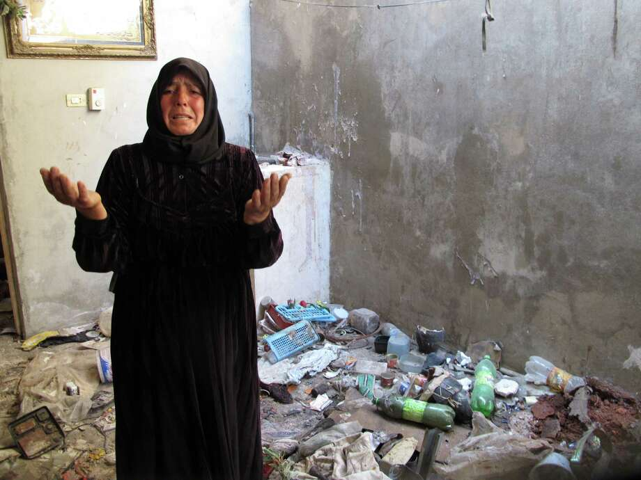 In this photo from Sunday, Aug. 5, 2012, Fatoum Obeid, 50, stands in a pile of trash left by Syrian soldiers who occupied her home in Atarib, Syria. In recent months rebels have seized a huge swath of territory in northern Syria, giving them a freedom to move and organize unprecedented in the 17-month conflict. (AP Photo/Ben Hubbard) Photo: Ben Hubbard / AP