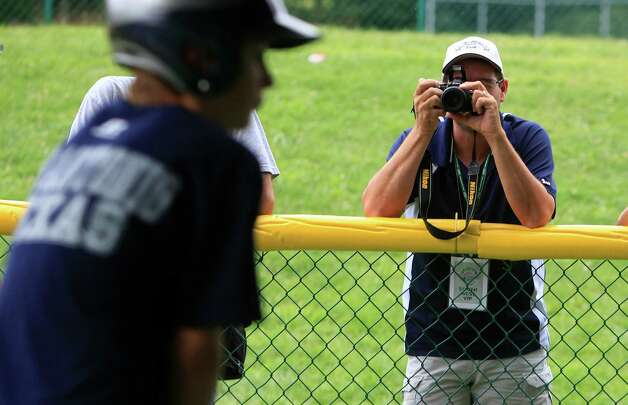 McAllister Park Little League parent Kenny Montemayor photographs the team as they hit the batting cages, Thursday, Aug. 27, 2009 in South Williamsport, Pa. Photo: Jerry Lara, San Antonio Express-News / glara@express-news.net