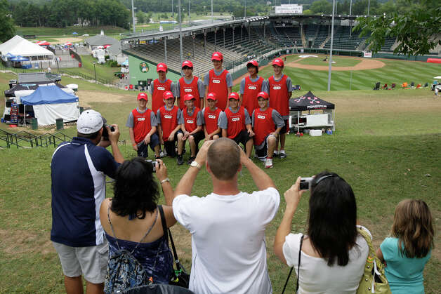 McAllister Park Little League parents photograph the team with sponsor T-shirts at the International Little League Complex, Thursday, Aug. 27, 2009 in South Williamsport, Pa. Photo: Jerry Lara, San Antonio Express-News / glara@express-news.net