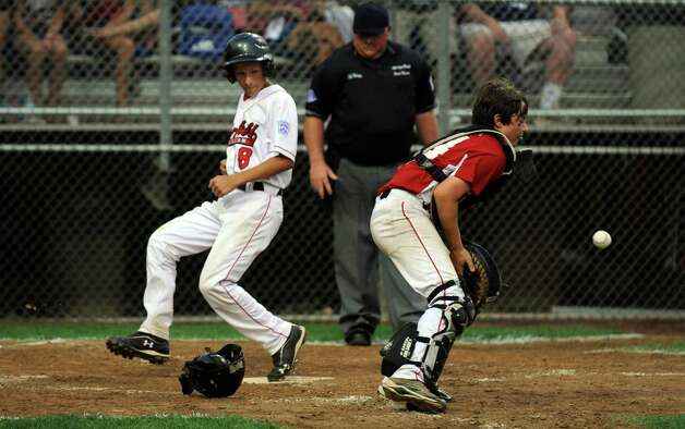 Fairfield American's Henry Prestegaard crosses home plate as Bedford catcher Connor Zendzian waits for the ball Saturday August 11, 2012 during the New England Regional championship at Breen Field in Bristol, Conn.  Fairfield beat Bedford 14-0. Photo: Autumn Driscoll / Connecticut Post