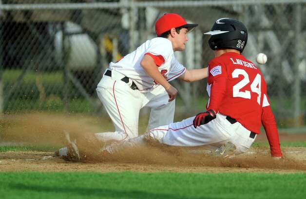 Fairfield American's Kevin Oricoli waits for the ball as Bedford Little League's Grant Lavigne slides to third Saturday August 11, 2012 during the New England Regional championship at Breen Field in Bristol, Conn.  Fairfield beat Bedford 14-0. Photo: Autumn Driscoll / Connecticut Post