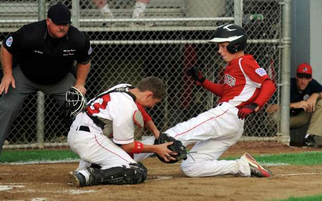 Fairfield American catcher Biagio Paoletta tags Bedford's Grant Lavigne out at home plate Saturday August 11, 2012 during the New England Regional championship at Breen Field in Bristol, Conn.  Fairfield beat Bedford 14-0. Photo: Autumn Driscoll / Connecticut Post