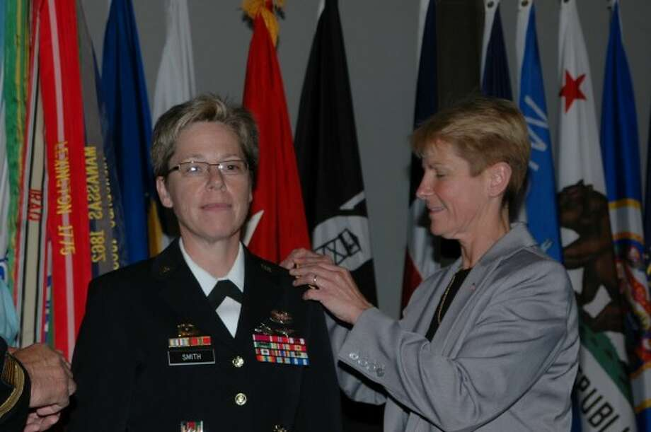 Tracey Hepner, co-founder of the Military Partners and Families Coalition, pins on her wife's first star during Brig. Gen. Tammy Smith's promotion on Saturday. Photo: OutServe Magazine