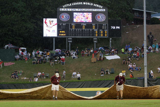 Workers cover the field at Lamade Stadium as rain fall before the McAllister Park-Staten Island, N.Y., semifinals at Lamade Stadium in the 2009 Little League Baseball World Series, Wednesday, Aug. 26, 2009 in South Williamsport, Pa. Photo: Jerry Lara, San Antonio Express-News / glara@express-news.net