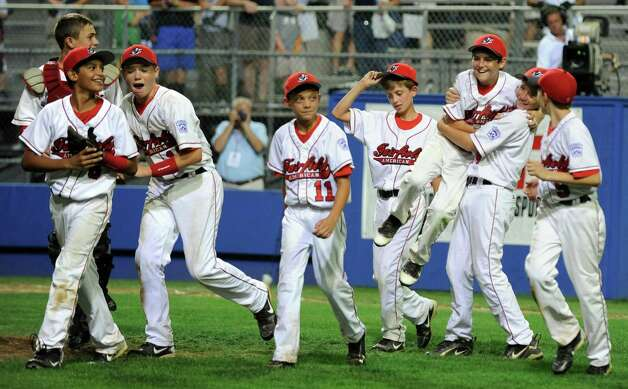 Fairfield American players celebrate their 14-0 win over Bedford Little League, of New Hampshire, Saturday August 11, 2012 in the New England Regional championship at Breen Field in Bristol, Conn. Photo: Autumn Driscoll / Connecticut Post
