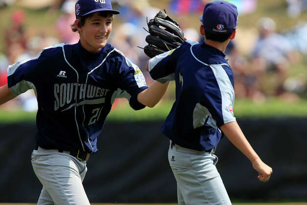 McAllister Park shortstop Steven Cardone high-fives third baseman Troy Montemayor after Montemayor caught a line drive from Logan County/Russellville Little League catcher Matt Harper to end the top of the third inning, Sunday, Aug. 23, 2009 in South Williamsport, Pa. McAllister took their second game of pool play 12-0 in the 2009 Little League Baseball World Series. Photo: Jerry Lara, San Antonio Express-News / glara@express-news.net
