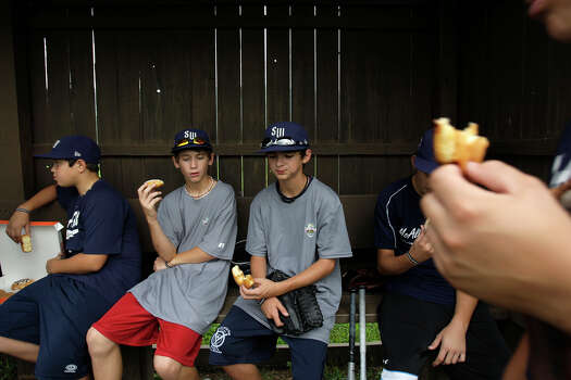 McAllister Park players John Shull (from left), Tanner Scarborough and Zach Morrow take a doughnut break during morning practice, Saturday, Aug. 22, 2009. After winning their first game against Peabody Western 10-1 Friday night, they will face off with Logan County/Russellville Little League Sunday afternoon. Photo: Jerry Lara, San Antonio Express-News / glara@express-news.net