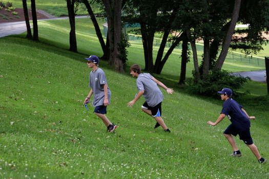 McAllister Park Little League's Wyatt Willis (from left), Steven Cardone and John Shull tire out after chasing a rabbit on a hill near thier dorms in South Williamsport, Pa., Wednesday, Aug. 19, 2009. Photo: Jerry Lara, San Antonio Express-News / glara@express-news.net