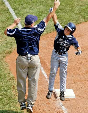 McAllister Park manager Mike Shull (left) gives Nicholas Smisek (6) a high-five as he rounds third base after hitting a grand slam off Russellville, Ky., pitcher Zach Denney during Little League World Series baseball pool play in South Williamsport, Pa., Sunday, Aug. 23, 2009. McAllister Park won 12-0. Photo: Gene J. Puskar, Associated Press / AP