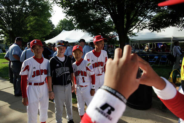 McAllister Park Little League player Kyle Pollard poses with players from Japan during a picnic held before the fifth annual Grand Slam Parade through Williamsport, Pa., Thursday, Aug. 20, 2009. Photo: Jerry Lara, San Antonio Express-News / glara@express-news.net