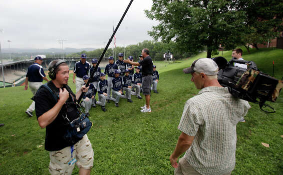 ESPN's soundman Brian Connolly (left) and cameraman Jeff Alred capture moments as McAllister Park Little League meets for official team photos and interviews by national media by Howard J. Lamade Stadium in South Williamsport, Pa., Thursday, Aug. 20, 2009. Photo: Jerry Lara, San Antonio Express-News / glara@express-news.net
