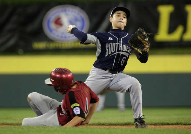 McAllister Park second baseman Nicholas Smisek attempts a double play after tagging out New England's Michael Petrosinio during the first round of Pool Play of the 2009 Little League World Series in South Williamsport, Pa., Friday, Aug. 21, 2009. McAllister won 10-1. Photo: Jerry Lara, San Antonio Express-News / glara@express-news.net