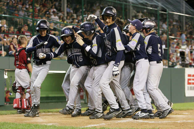 McAllister Park right fielder Jacob Ramos (16) is mobbed after his home run brought in three runs against New England during the first round of Pool Play of the 2009 Little League World Series in South Williamsport, Pa., Friday, Aug. 21, 2009. McAllister won 10-1. Photo: Jerry Lara, San Antonio Express-News / glara@express-news.net