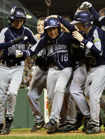 McAllister Park batter Jacob Ramos (16) is mobbed by teammates as he crosses the plate after hitting a three-run home run in the fourth inning against Peabody, Mass., during pool play of the Little League World Series Friday, Aug. 21, 2009, in South Williamsport, Pa. McAllister Park won 10-1. Photo: Carolyn Kaster, Associated Press / AP