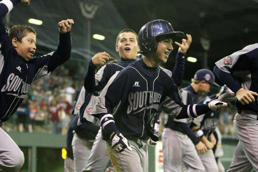 McAllister Park's Jacob Ramos (center), John Shull (left) and Nicholas Smisek celebrate after Ramos hit a home run bringing in three runs against New England during the first round of Pool Play of the 2009 Little League World Series in South Williamsport, Pa., Friday, Aug. 21, 2009. McAllister won 10-1. Photo: Jerry Lara, San Antonio Express-News / glara@express-news.net