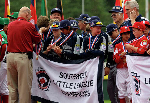 McAllister Park players Kyle Pollard (at the front, from left) and Drew Brooks check out their World Series Participant medals while Wyatt Willis checks out the Canadian team during the Opening Ceremonies of the 2009 Little League Baseball World Series in South Williamsport, Pa., Friday, Aug. 21, 2009. Photo: Jerry Lara, San Antonio Express-News / glara@express-news.net