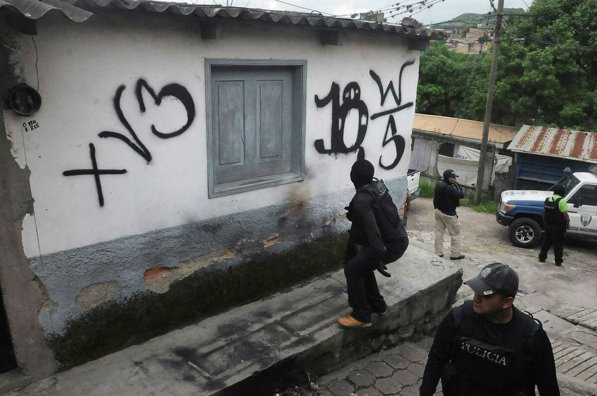 The National Police reclaim a home that had been seized by gangs in the 14 de Marzo neighborhood in Tegucigalpa, Honduras. Gang members seized the home after the owners fled, unable to pay extortion fees.