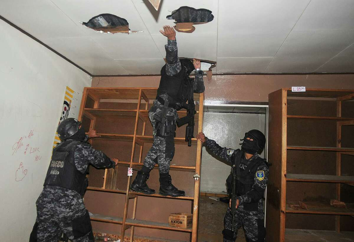 In this June 14, 2012 photo, national police inspect a home that had been seized by gangs in the 14 de Marzo neighborhood in Tegucigalpa, Honduras. Gang members seized the home after the rightful owners fled, unable to pay their extortion fees. Extortion of homeowners is a chilling new crime trend in Honduras, already among the world?s most dangerous countries. By demanding people pay to stay in their own homes, gang members have emptied some neighborhoods and have changed the way many live. (AP Photo/Fernando Antonio)
