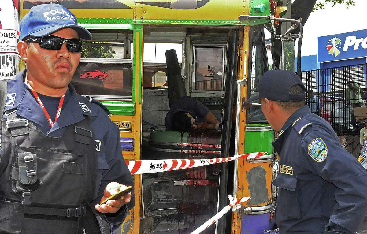 In this Aug. 6, 2012 photo, national police stand at a crime scene where a public bus driver was slain by an unidentified attacker in Tegucigalpa, Honduras. According to police on the scene, the driver was a probable victim of gang extortion, which is common throughout Central America. In Honduras, taxi drivers and business owners are also used to extortion, but the practice now has reached into the one place many people considered their last remaining safe haven: their home. (AP Photo/Fernando Antonio)