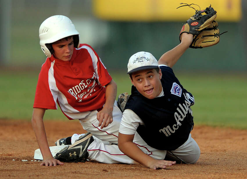 McAllister Park second baseman Nick Smisek (right) watches his throw reach first in time to complete a double-play. Matthew Kress of Bridge City also watches. McAllister Park won the game, 6-4, in Waco, to advance to the Little League World Series. Aug. 14, 2009.