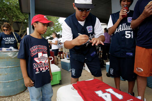Gabriel Palos, 8, gets an autograph from McAllister Park Little League team member Travis Daves during a meet-an-greet, Sunday, Aug. 16, 2009. In back is team member Drew Brooks. Palos wanted the autograph after watching the team on media reports. Photo: Jerry Lara, San Antonio Express-News / glara@express-news.net