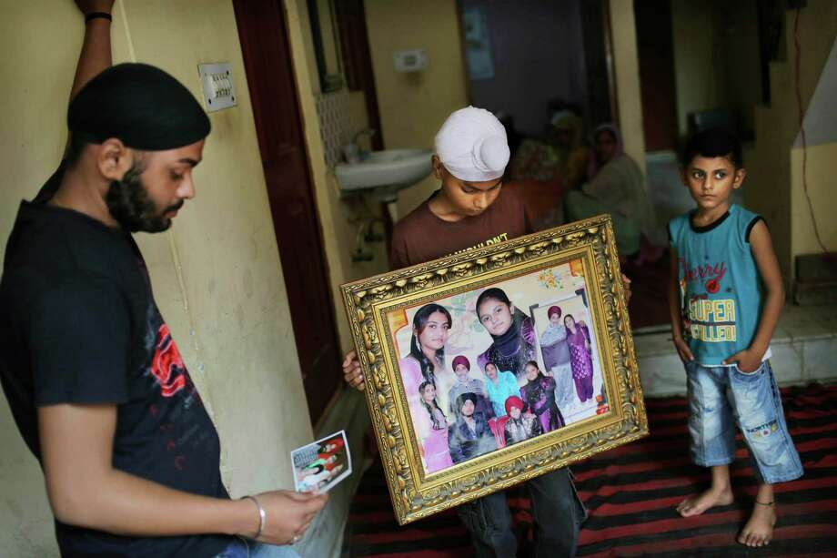 Indian relatives in New Delhi mourn brothers Sita and Ranjit Singh, who were killed in the shooting attack at a Sikh temple in Wisconsin. Ranjit Singh came to the U.S. 16 years ago but was still involved in their lives. Photo: Kevin Frayer / AP,